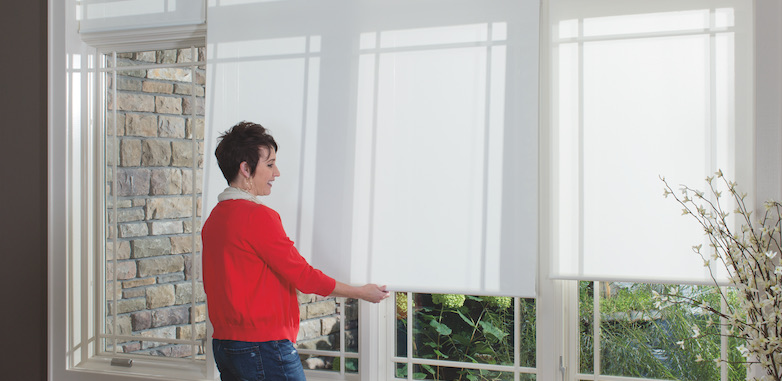 Woman pulling down window shades
